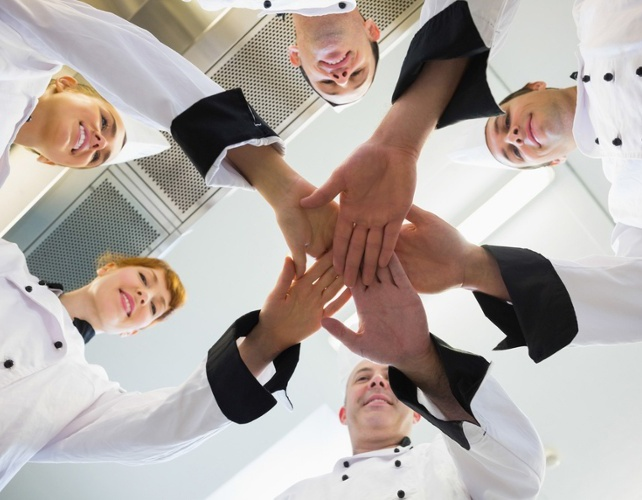 Chefs joining hands in a circle wearing uniforms in a kitchen